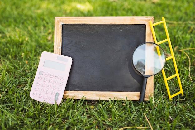 Lavagna vuota con calcolatrice e lente d'ingrandimento su erba