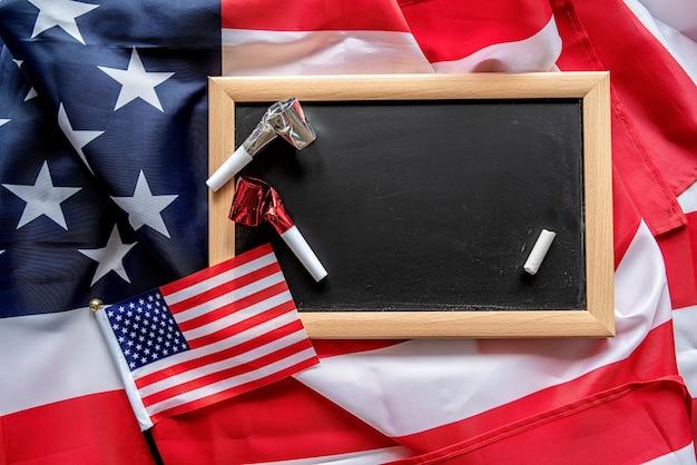 Lavagna vuota con un pezzo di un gesso bianco e noisemakers con bandiere americane