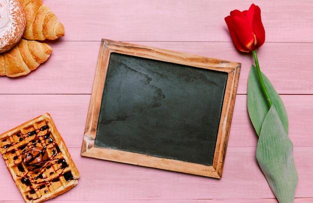 Lavagna vuota con waffle belga e tulipano