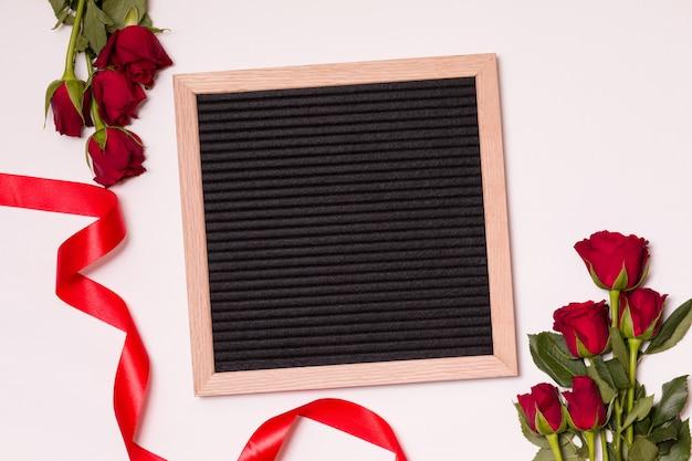 Lavagna vuota sul fondo di san valentino con rose rosse e nastro.
