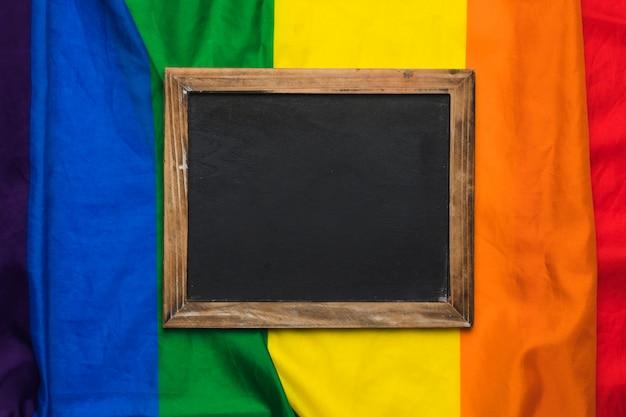Lavagna vuota sulla bandiera arcobaleno