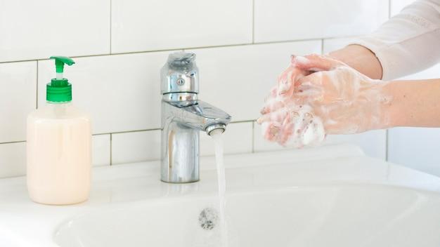 Lavandino del bagno con sapone liquido e lavarsi le mani