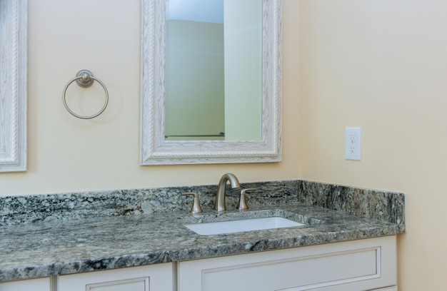 Lavandino elegante del progettista in bagno nella casa del lusso del contro rubinetto