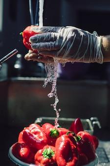 Lavare i peperoni rossi sotto la gru. foto di alta qualità