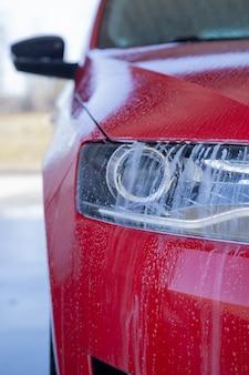 Lavare un'auto moderna con acqua e sapone ad alta pressione, pulire i fari
