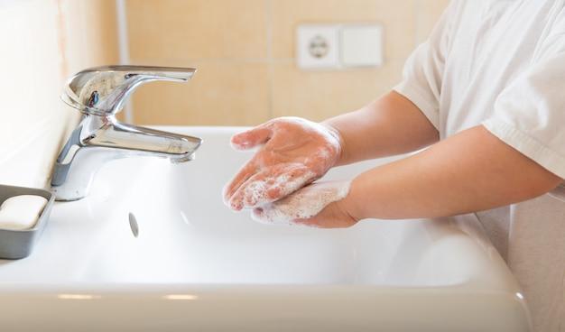 Lavarsi le mani sapone per il risciacquo del bambino con acqua corrente al lavandino, igiene delle mani di prevenzione del coronavirus.
