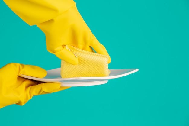 Lavastoviglie indossando guanti gialli su un blu.