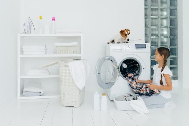 Lavatrice svuotamento ragazza positiva, tiene camicia a scacchi pulita, guarda con sorriso l'animale preferito che aiuta a fare il bucato, posa sul pavimento bianco con bacinella piena di vestiti, detergenti.