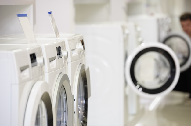Lavatrici nel negozio di elettrodomestici e acquirente sfocato