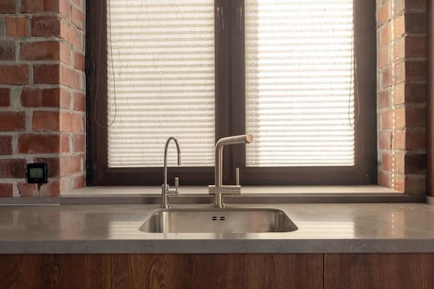 Lavello con pochi rubinetti accanto alla finestra e al muro di mattoni