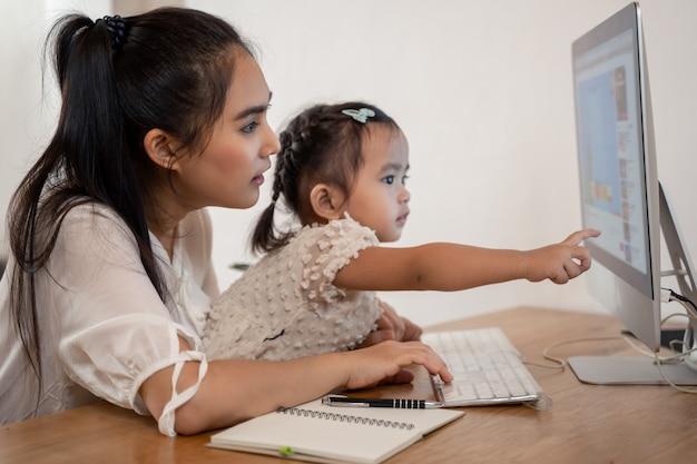 Lavora da casa concetto. madre e figlia che per mezzo di un computer e di internet durante la madre che lavora dalla casa