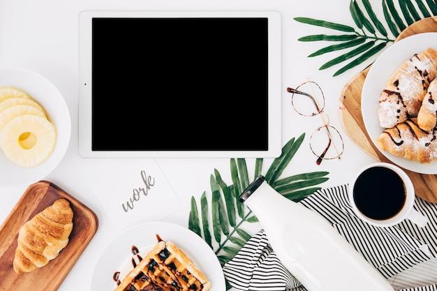Lavora il testo su carta vicino alla tavoletta digitale; fette di ananas; croissant; cialde; bottiglia; tazza di caffè e occhiali sulla scrivania bianca