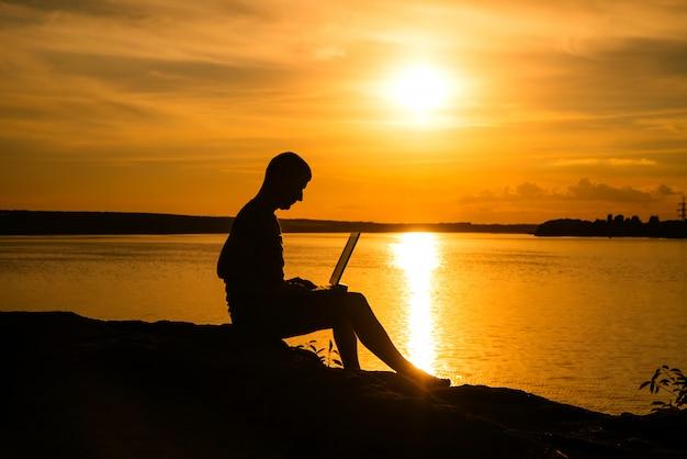 Lavora in vacanza con un computer portatile vicino al fiume al bel tramonto.