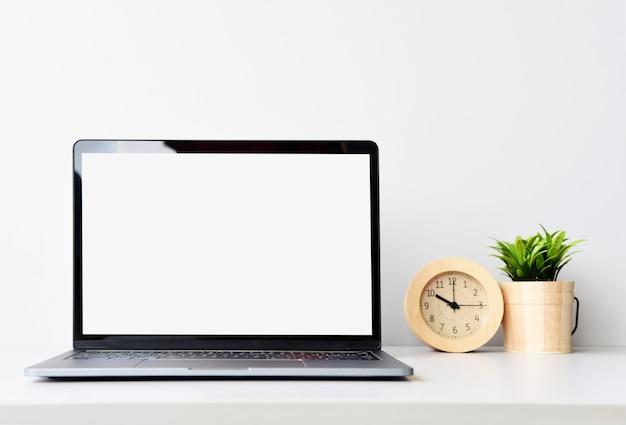 Lavorando con il computer portatile sulla scrivania nella stanza bianca