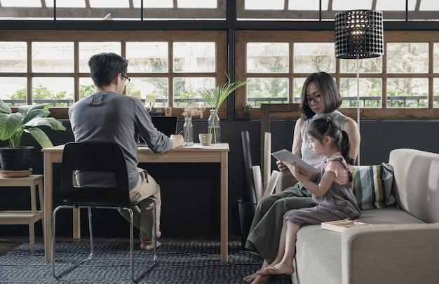 Lavorando da casa stile di vita padre usando il portatile sulla scrivania e bambina che impara con sua madre sul divano in salotto, isolamento in quarantena durante la crisi sanitaria di coronavirus (covid-19)