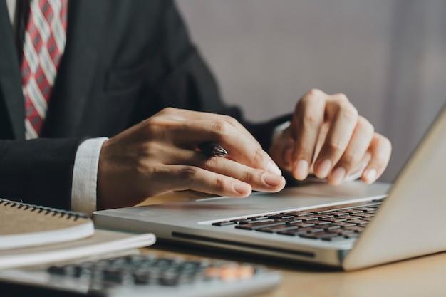 Lavorando sul portatile, vicino delle mani di uomo d'affari utilizzando il computer portatile. concetto di finanza