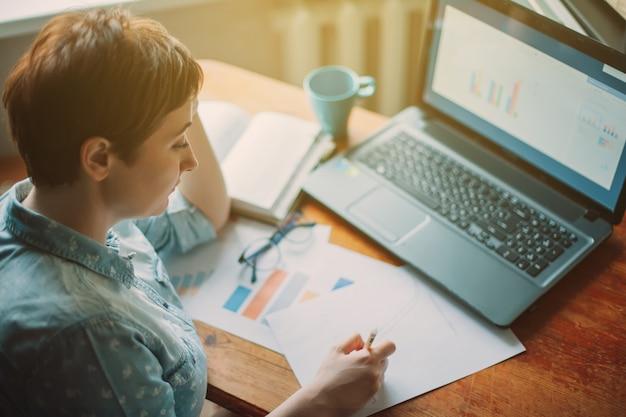 Lavorare a casa. analista del ragioniere di donna che fa analisi del grafico nell'affare, sedentesi alla tavola con il computer portatile