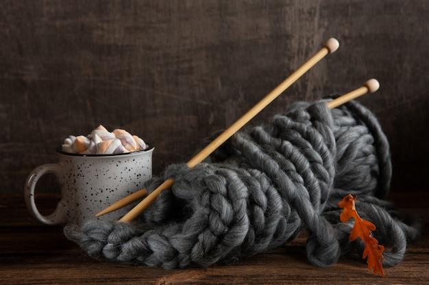 Lavorare a maglia con spessi fili grigi su ferri da maglia in legno e una tazza con una bevanda calda e marshmallow,