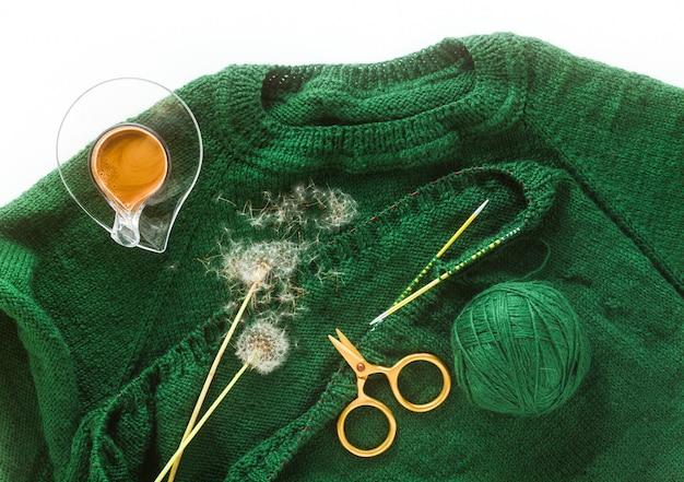Lavorare a maglia un maglione con ferri da maglia e una tazza di caffè. sfondo per filati e maglieria