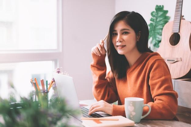 Lavorare creativo della giovane donna asiatica al computer portatile di mattina - lavorando dal concetto domestico