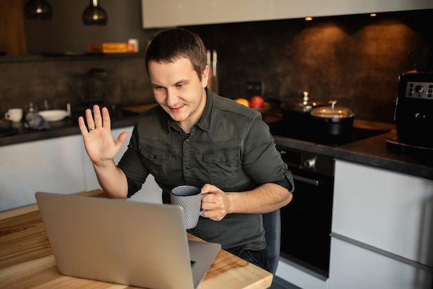 Lavorare da casa. il lavoratore conduce una videochiamata, una videoconferenza con i suoi colleghi sul portatile in casa