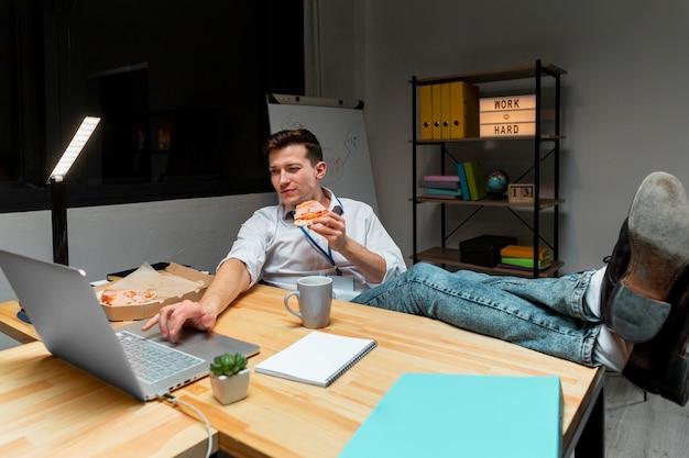 Lavoratore adulto che mangia pizza mentre lavorando dalla casa