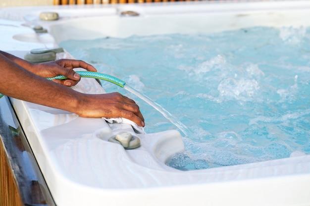 Lavoratore africano del personale dell'hotel che pulisce la piscina