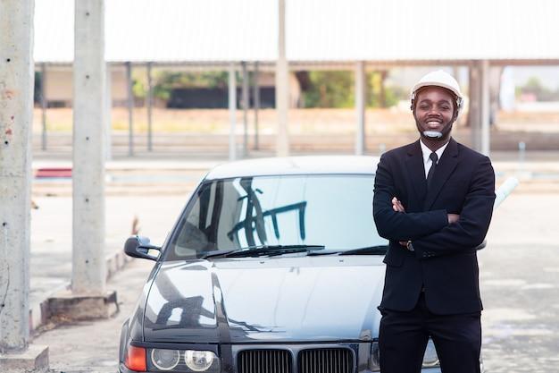 Lavoratore africano dell'ingegnere di costruzione dell'uomo che sta con l'automobile
