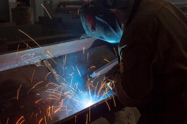 Lavoratore al primo piano di saldatura di fabbrica scintille industriali