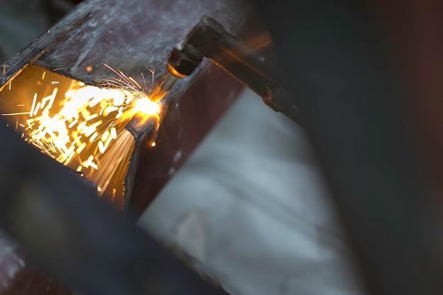 Lavoratore asiatico che fa le scintille mentre saldando acciaio