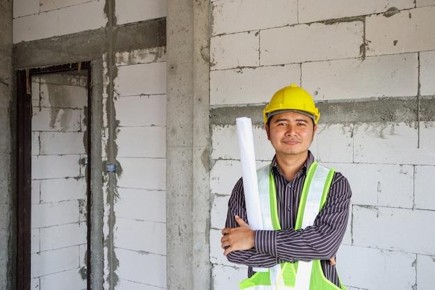 Lavoratore asiatico dell'ingegnere di costruzione dell'uomo di affari nel casco protettivo e carta delle cianografie a disposizione al cantiere della casa