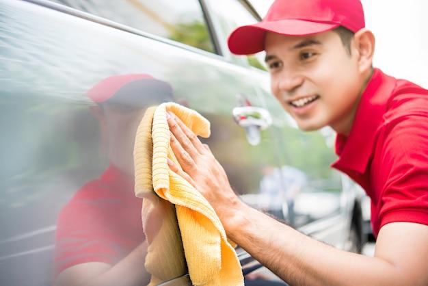 Lavoratore asiatico dell'uomo in un'uniforme rossa che pulisce felicemente un'automobile con un panno giallo della microfibra