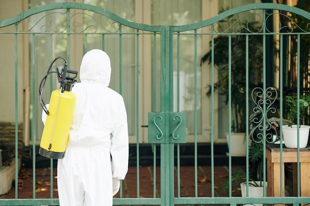 Lavoratore che disinfetta i cancelli della casa