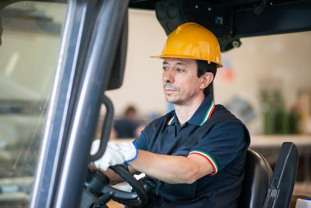 Lavoratore che fa funzionare un carrello elevatore industriale in una struttura