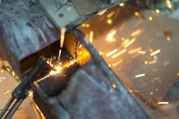 Lavoratore che fa scintille dalla saldatura dell'acciaio nel posto di lavoro.