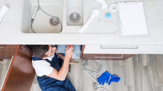 Lavoratore che giace sotto il lavello della cucina