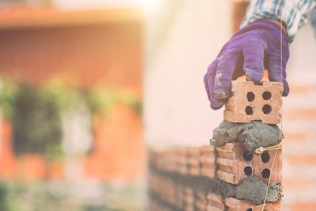 Lavoratore che installa la parete di mattoni in corso della costruzione di casa