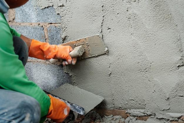 Lavoratore che intonaca cemento sulla parete per la costruzione della casa