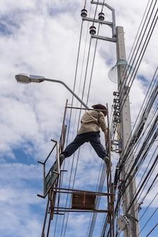 Lavoratore che lavora per installare la linea elettrica