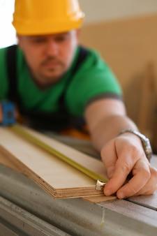 Lavoratore che misura il legno