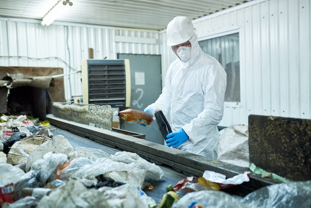 Lavoratore che ordina il cestino sul piano di elaborazione dei rifiuti