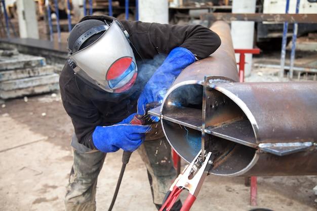 Lavoratore che salda in una fabbrica. saldatura su un impianto industriale.