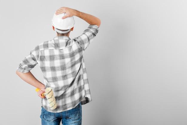 Lavoratore che sembra sconcertante una parete in bianco
