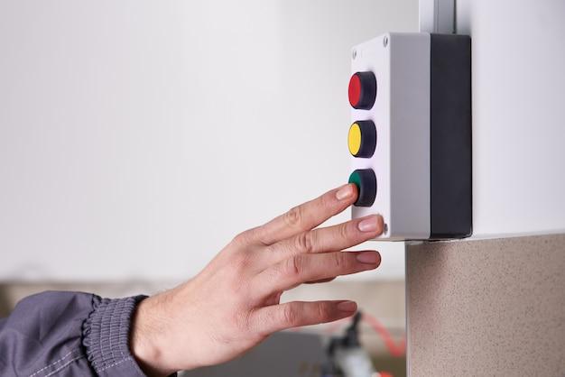 Lavoratore che spinge bottone verde che fa funzionare una macchina in una fabbrica, fine su della mano