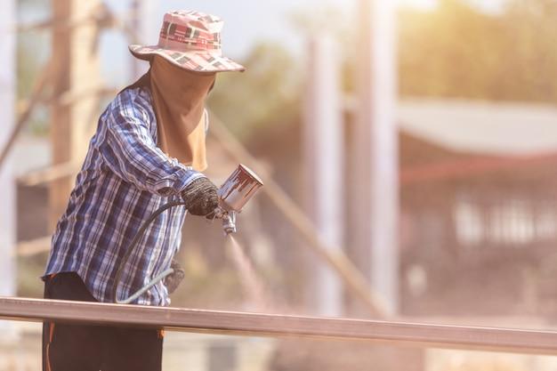 Lavoratore che spruzza la vernice sul tubo d'acciaio per impedire la ruggine sulla superficie