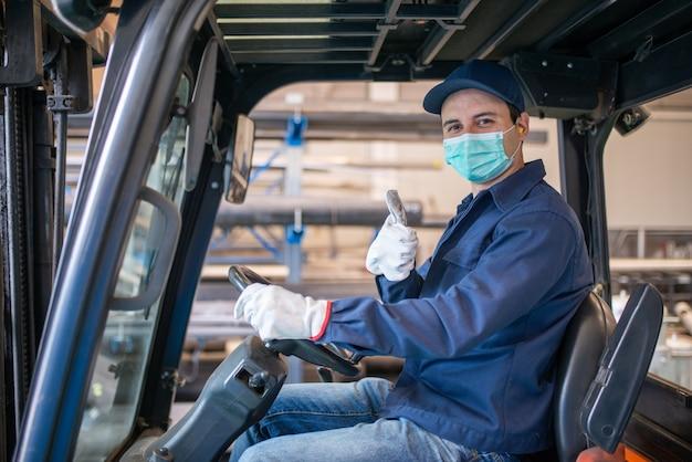 Lavoratore che utilizza un carrello elevatore, conducente al lavoro in una fabbrica industriale