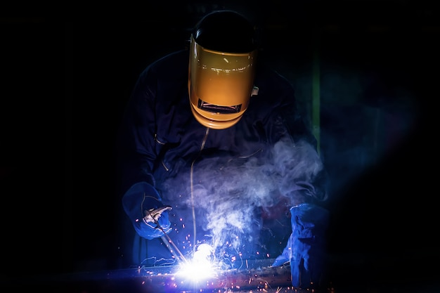 Lavoratore circa l'acciaio del saldatore usando la saldatrice elettrica.