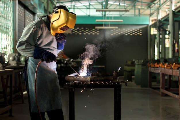 Lavoratore circa l'acciaio del saldatore usando la saldatrice elettrica
