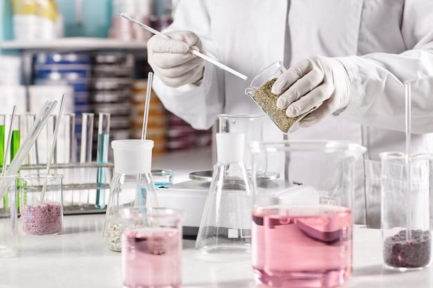 Lavoratore circondato da bicchieri di vetro pieni di liquido colorato