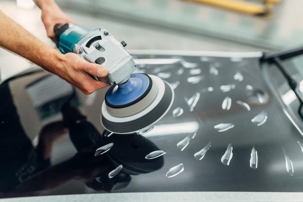 Lavoratore con lucidatrice pulisce il cofano dell'auto